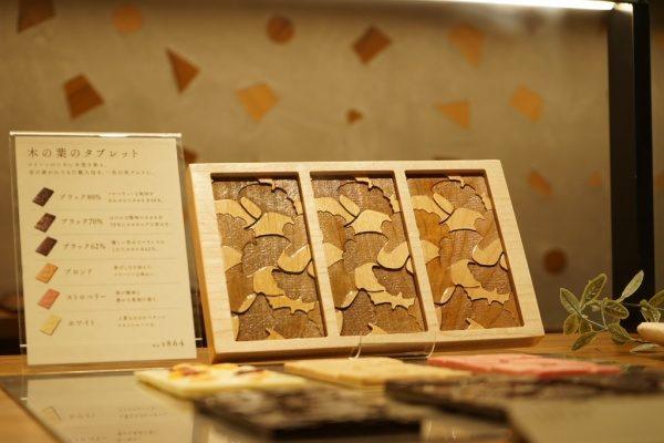 カウンターの上の木の葉のタブレット用のチョコレート木型、後ろ側は木片入りのモラート仕上げの壁