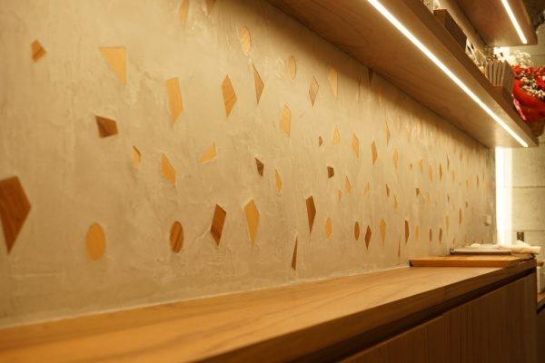 木片入りのモラート仕上げの壁、棚が取り付けてあり二段目には花がある