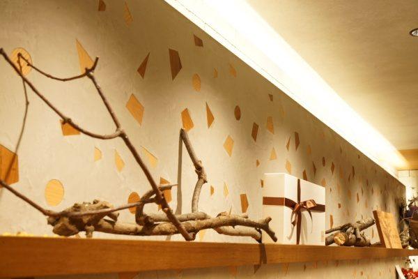 木片入りのモラート仕上げの壁、棚にはチョコレートショップの包装された商品や木の枝が並んでいる