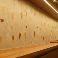 木片入りのモラート仕上げの壁、棚が取り付けてある