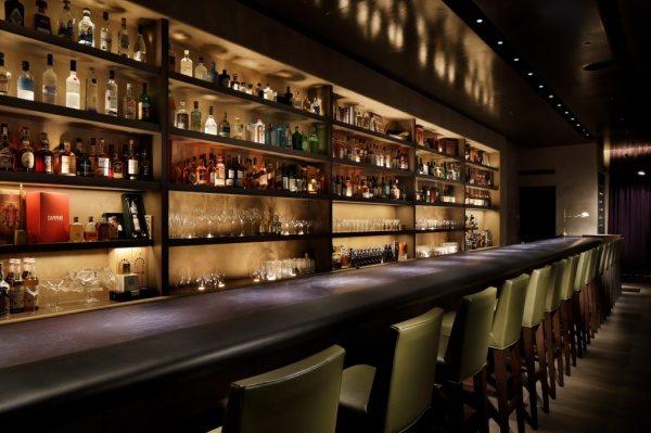日比谷ミッドタウンスターバーのモールテックスのバーカウンター、手前には椅子が並び、奥の棚には酒瓶やグラスが並んでいる