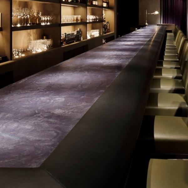 日比谷ミッドタウンスターバーのモールテックスのバーカウンター、右側には椅子が並び、左の棚には酒瓶やグラスが並んでいる