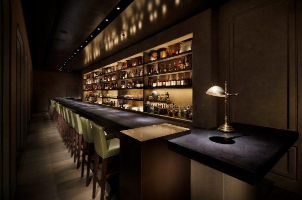 日比谷ミッドタウンスターバーのモールテックスのバーカウンター、右手前には照明があり、左手前には椅子が並び、奥の棚には酒瓶やグラスが並んでいる