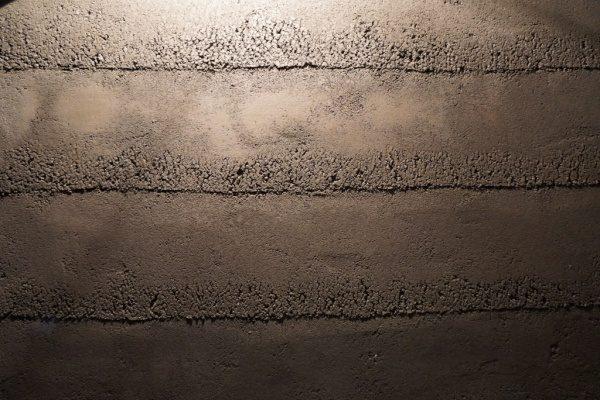 塗り版築で施工したお店のエントランスの壁、正面からのアングル、少し段差を付けてあり型枠のバラツキを表現している