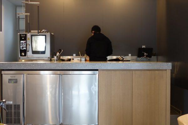 ビールストーンテラクリスタマジェスティックゴールドキッチン天板、神奈川県小田原mecimo、周りに調味料や調理器具、一人の人物が調理場に立っている
