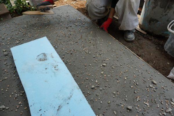 モルタル三和土風仕上げ、鏝で石を埋め込んでならしている様子
