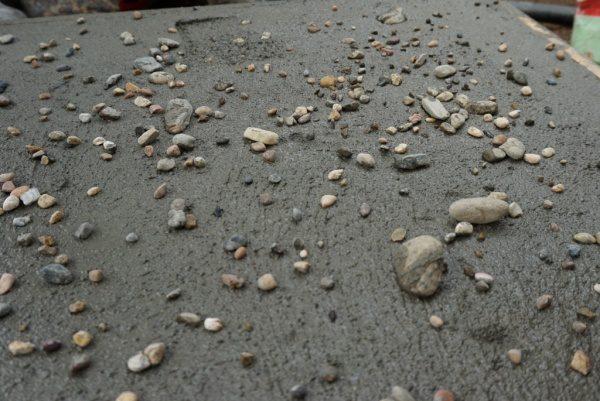 モルタル三和土風仕上げ、石を埋め込み済みの箇所とこれから石を埋め込む箇所がある状態