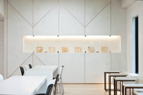 白いモールテックスの壁、正面に展示品、左手前に2組の机と椅子、右に窓、右手前にベンチと机