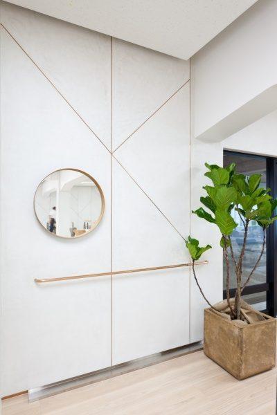 白いモールテックスの壁、手すりが付いている、観葉植物がありその後ろに窓がある、右側に鏡がある
