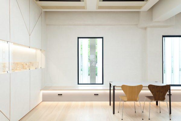 白いモールテックスの壁、正面に窓がありその下にはベンチ、左に展示品、右手前に机と椅子