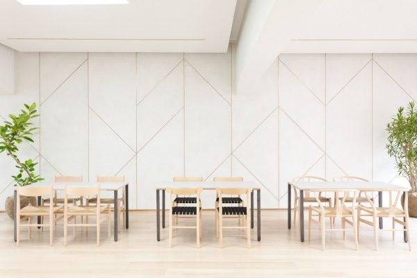 白いモールテックスの壁、3組の机と椅子があり両端に観葉植物