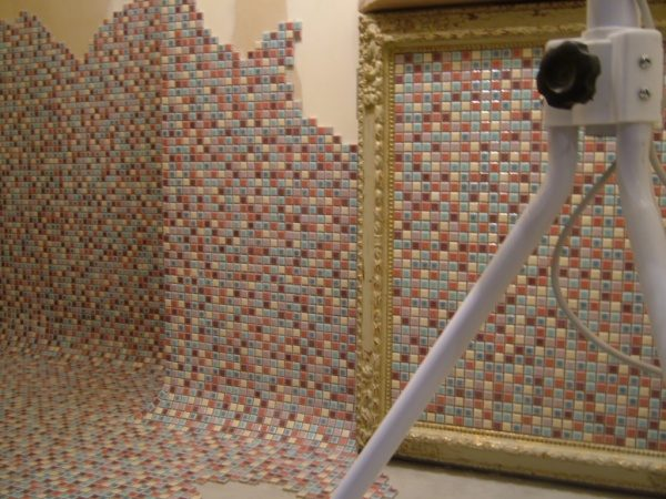 モザイクタイルの壁と床、タイルで繋がりを曲面で繋げている、手前に三脚のようなものがある