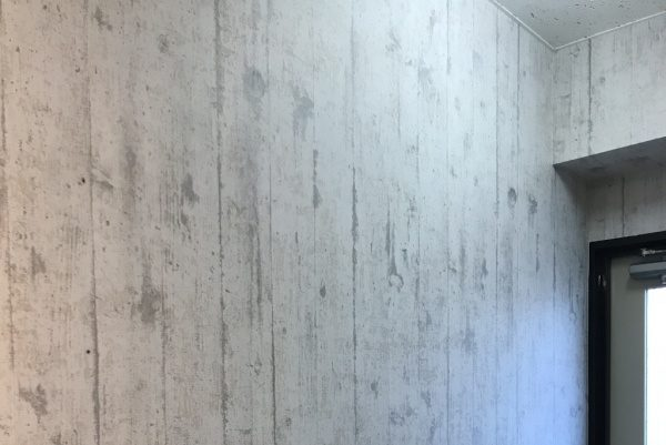 施工前の壁、コンクリート調に見えるビニルクロスが貼られた壁