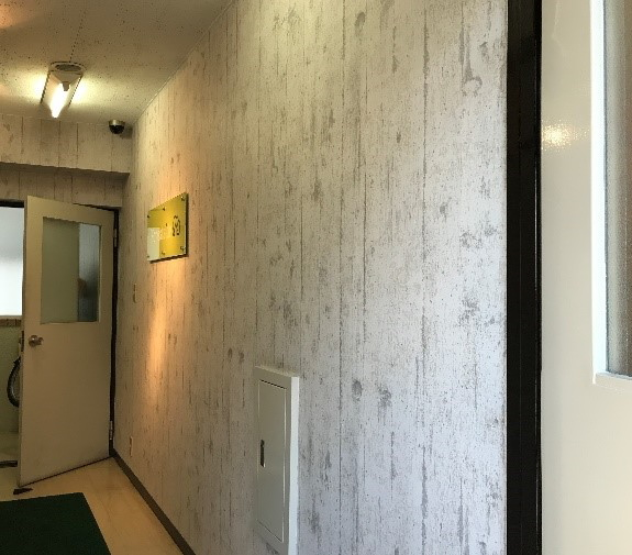施工前の壁、コンクリート調に見えるビニルクロスが貼られた壁、鉄製の点検口がある