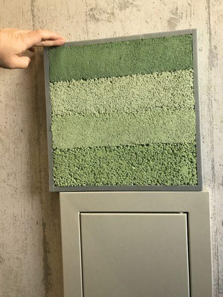 緑色の塗り版築仕上げサンプル見本と施工前の壁の状態、下は点検口