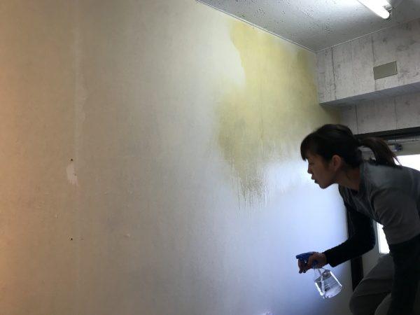 壁に水を吹きかけている原田左官の福吉さん