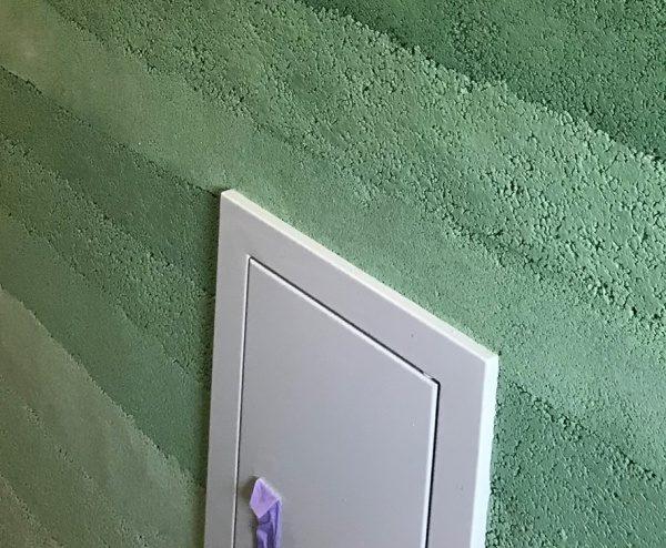 緑色の塗り版築仕上げ壁、自然光で見た状態の壁、点検口がある