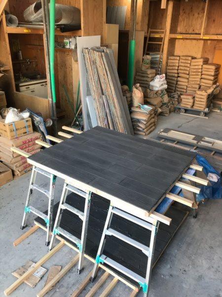 うづくり木目モルタルで施工したパネル、周りには材料や道具が並んでいる