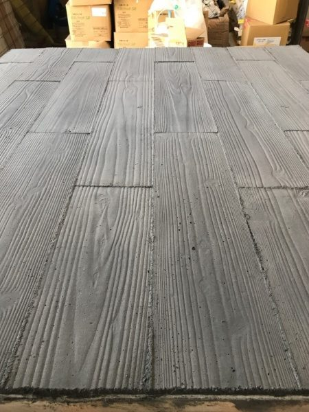 うづくり木目モルタルで施工したパネル、周りには材料が並んでいる