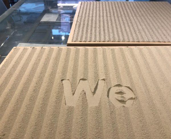 樹脂左官材で櫛引仕上げをしたWe抜き文字仕上げサンプル、上側に通常の櫛引仕上げのサンプル