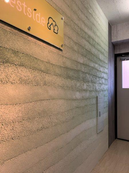 塗り版築のオフィスエントランス壁、壁には東京都蒲田のフォレストサイド様のロゴ看板、右に扉