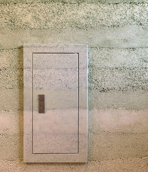 塗り版築のオフィスエントランス壁、点検口はデコラティブペイントで版築に合わせた色で施工されている