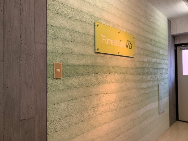 オフィスエントランスの壁、左がうづくり木目モルタルの壁、右側が塗り版築の壁、東京都蒲田のフォレストサイド様のロゴ看板