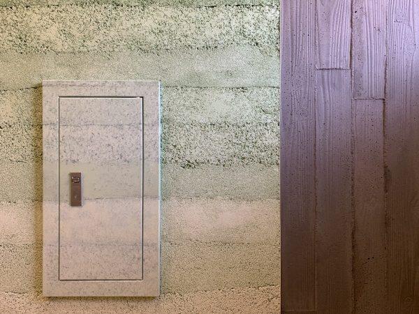 オフィスエントランスの壁、左が塗り版築の壁、右がうづくり木目モルタルの壁、点検口はデコラティブペイントで版築に合わせた色で施工