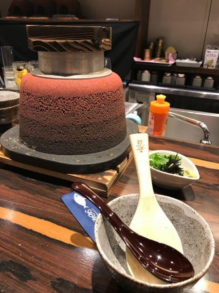 赤の版築かまど、横に小鉢、手前にスプーンとしゃもじ、SABAR+ 大阪京橋店