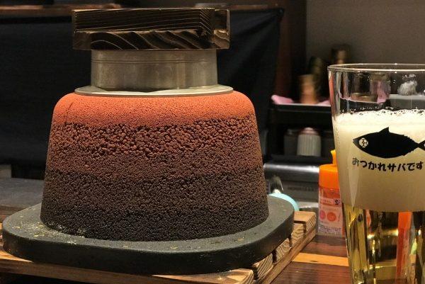 赤の版築かまど、横にビールが注がれたコップ、SABAR+ 大阪京橋店
