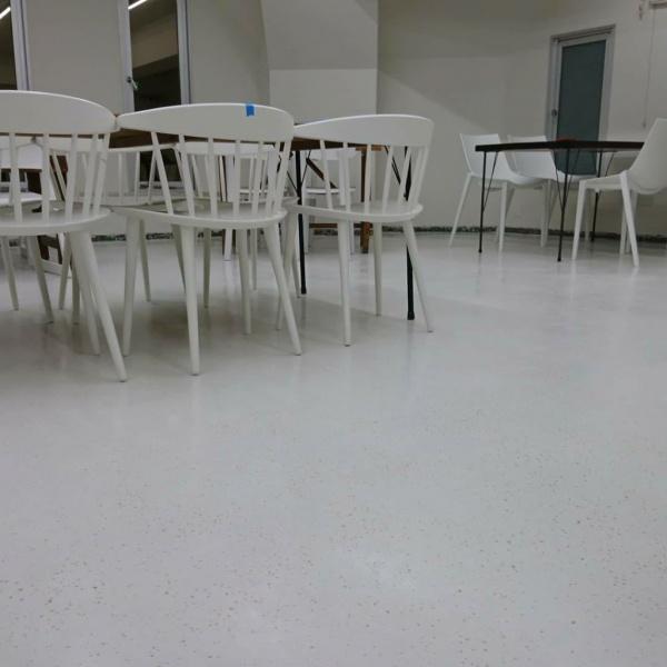 ビールストーン施工の打ち合わせサロンの床、机と椅子が並んでいる