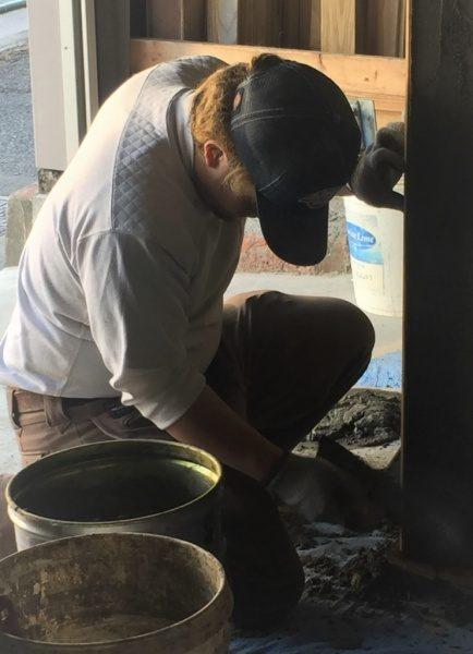 箱状のものにモルタルを塗り付けている原田左官の見習いさん