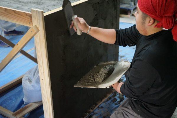 板状のものにモルタルを塗り付けている原田左官の見習いさん