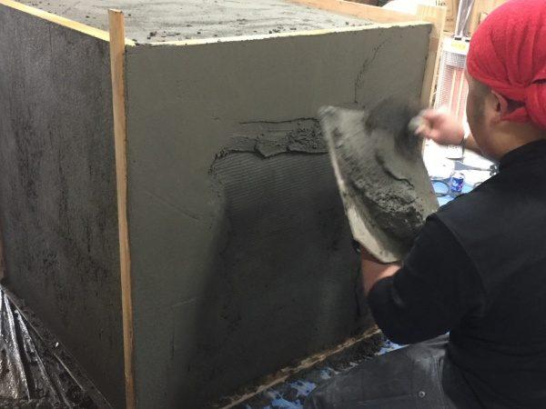 壁面に鏝でモルタルを塗り付けている原田左官の見習いさん