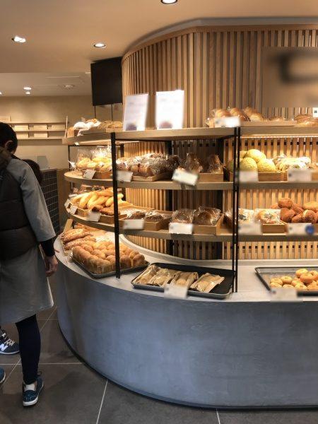 パン屋さんのモールテックスグレーのディスプレイ台、台の上にパンが沢山乗っている、店内風景