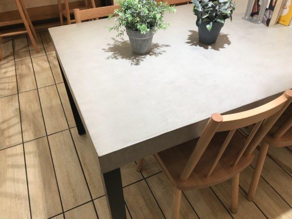パン屋さんのモールテックスグレーのテーブル、机の上には観葉植物や本が置いてある、周りに椅子もある、上からのアングル