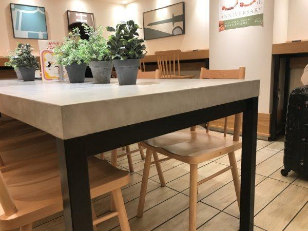 パン屋さんのモールテックスグレーのテーブル、机の上には観葉植物や本が置いてある、周りに椅子もある、側面からのアングル