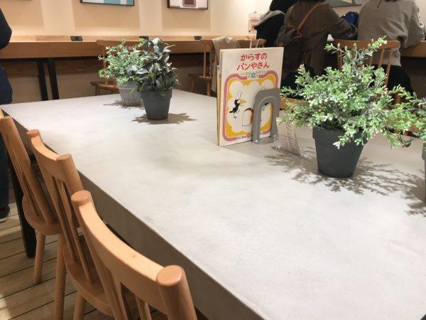 パン屋さんのモールテックスグレーのテーブル、机の上には観葉植物や本が置いてある、周りに椅子もある、絵本がある