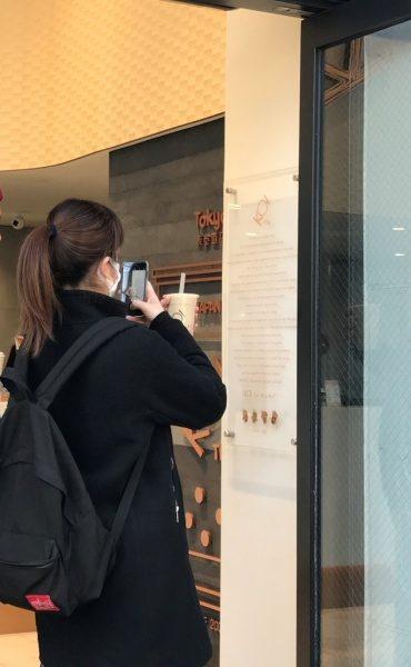 タピオカティーの店舗KOIティーの塗り版築壁面。それを撮影する女性