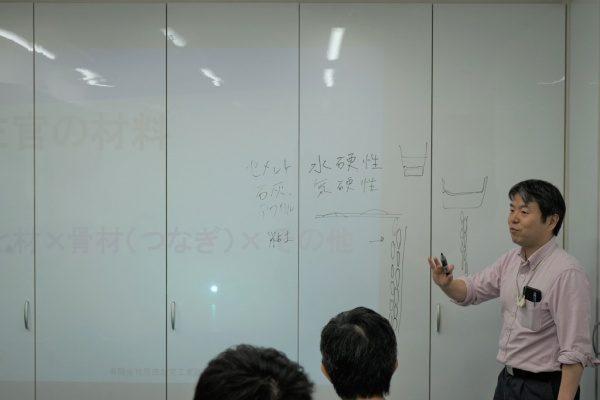 リノベーションカレッジで左官座学風景、講師の原田左官代表原田宗亮と受講生の方々、壁に映像投影と文字が書かれている