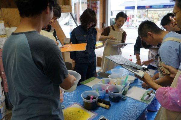 リノベーションカレッジで見本作り風景、見本作成をする受講生の方々、机に見本や着色材料
