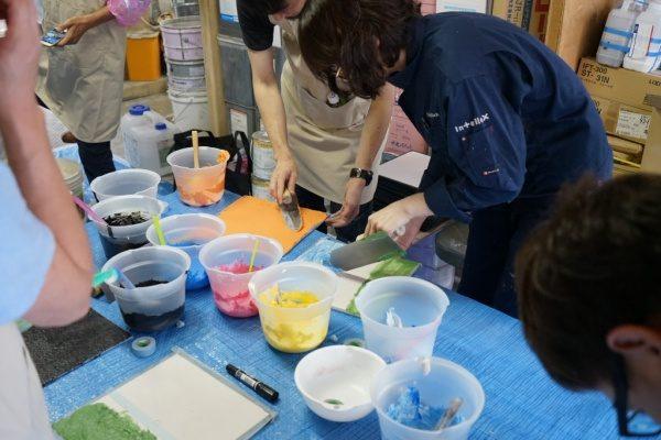 リノベーションカレッジで見本作り風景、見本作成をする受講生の方々、机に見本や着色材料、漆喰をカラフルに着色している