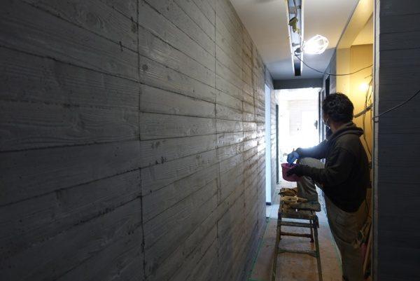 うづくり木目モルタルのエントランス壁、職人さんが足場に片足を乗せている