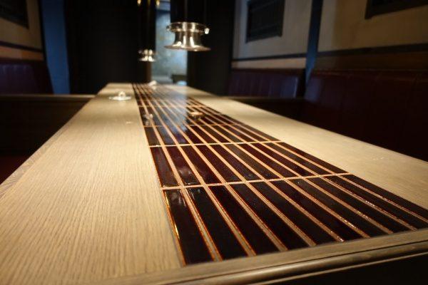 飲食店のテーブル天板、天板の真ん中にはタイルで施工されている、左からのアングル