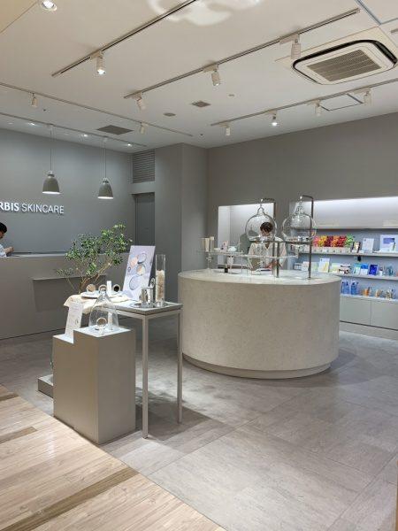ビールストーンの白・寒水石で施工した円形型ディスプレイ台、完成して化粧品店内に設置した状態、台上には商品がある。店内全体図
