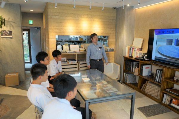 原田左官に企業訪問に来た中学校の生徒さんと応対する原田左官代表原田宗亮。モニターを使い左官の説明をしている