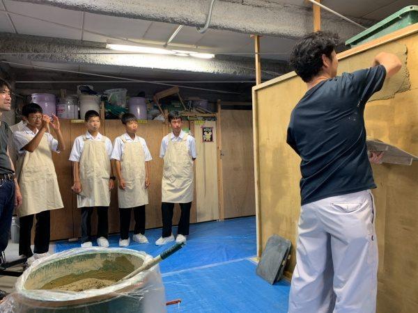 原田左官に企業訪問に来た中学校の生徒さんへ壁塗りの方法を説明する職人さん