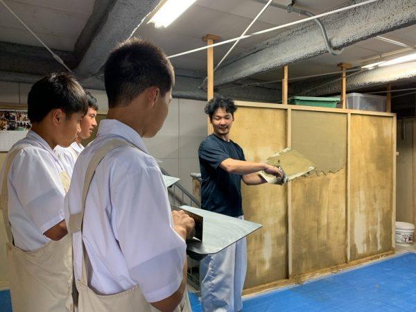 塗り体験をする中学校の生徒さん達に鏝返しの指導をする職人さん