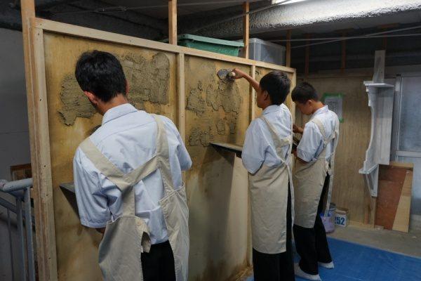 塗り体験で板に塗りつけている中学校の生徒さん達