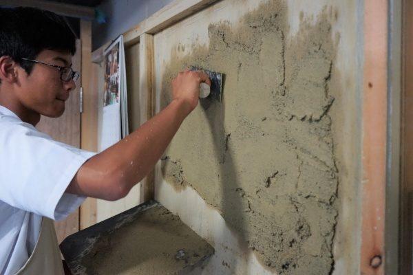 塗り体験で板に塗りつけている中学校の生徒さん。板に沢山材料が塗りつけられている
